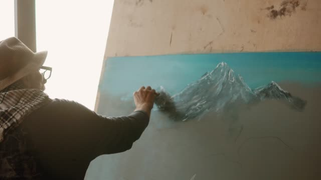 Old artist is drawing by white pastel mountains on a canvas