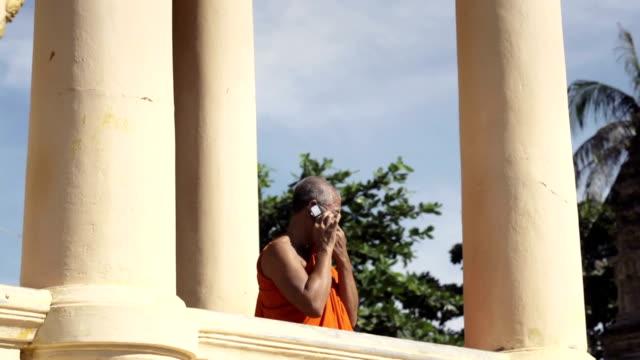 Antigua monje budista asiática hablando con el teléfono móvil en temple - vídeo
