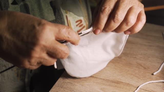 alte asiatische dame mit nadel für einen riemen auf eine maske setzen. herstellung von hausgemachten chirurgischen maske. schützen sie sich vor jeder krankheit. covid-19. coronavirus. - selbstgemacht stock-videos und b-roll-filmmaterial