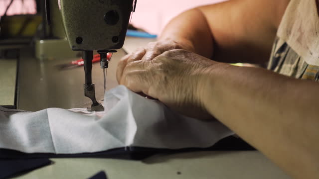 old asian lady using sewing machine for sewing a fabric. making a homemade surgical mask. fighting with any disease. covid-19. coronavirus. - cucitura video stock e b–roll