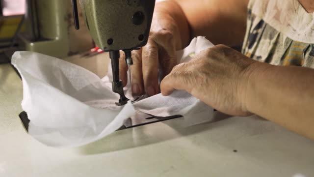 vídeos y material grabado en eventos de stock de vieja dama asiática usando la máquina de coser para coser una tela. haciendo una mascarilla quirúrgica casera. lucha contra cualquier enfermedad. covid-19. coronavirus. - montar
