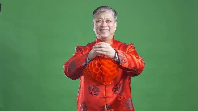 stary azjatycki człowiek w czerwony mandarin, szczęśliwy nowy rok 4 k - chinese new year filmów i materiałów b-roll
