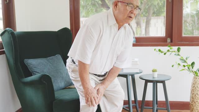 vídeos de stock, filmes e b-roll de velho asiático idoso sente dor, dor, dor no joelho enquanto está em pé e sentado em casa, conceito de osteoartrite - articulação humana