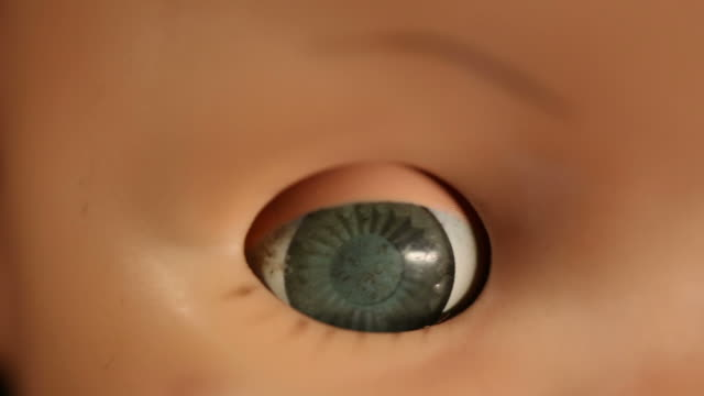 Old Baby Doll Eye Detail macro shot of an old baby doll face. camera moves around and racks focus doll stock videos & royalty-free footage