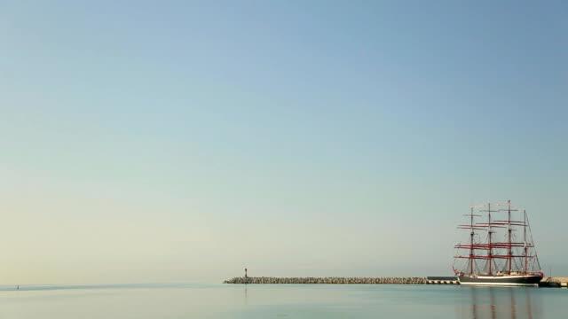 old bark at the port and lighthouse - dalgakıran stok videoları ve detay görüntü çekimi