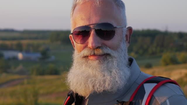 vecchio motociclista barbuto guarda la natura - barba peluria del viso video stock e b–roll