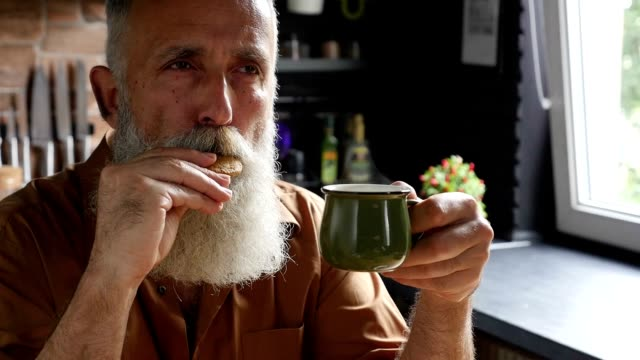 old bearded man drinking coffee and eating cookies in the kitchen an old man with a gray beard enjoys coffee and biscuits. he wears a shirt. on the back of the kitchen interior. one person.Slow motion cookie stock videos & royalty-free footage