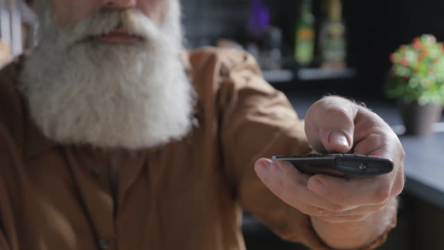 old bearded man with remote control in the kitchen