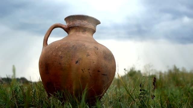 vidéos et rushes de vieux big clay jar restant sur l'herbe contre le fond de ciel - picto urne