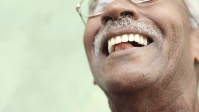 Old black man with glasses and mustache smiling video