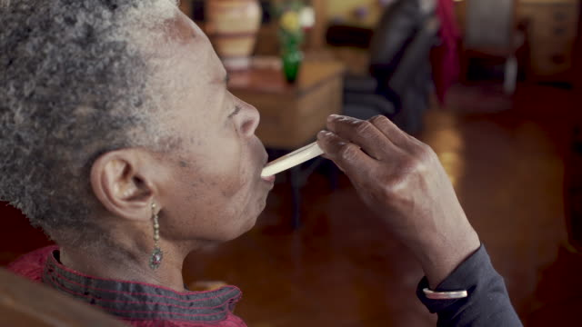 Old black woman putting a thermometer in her mouth - OTS