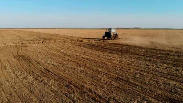 Gammal blå traktor med Harrow arbete i fält vid solnedgången och plöjning marken innan plantering video