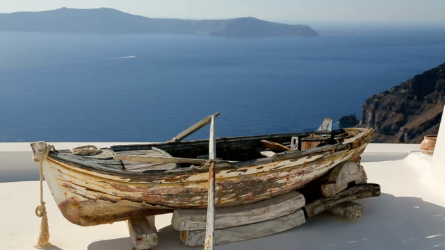 Old boat on roof of house in Oia town, sightseeing tour around Santorini island
