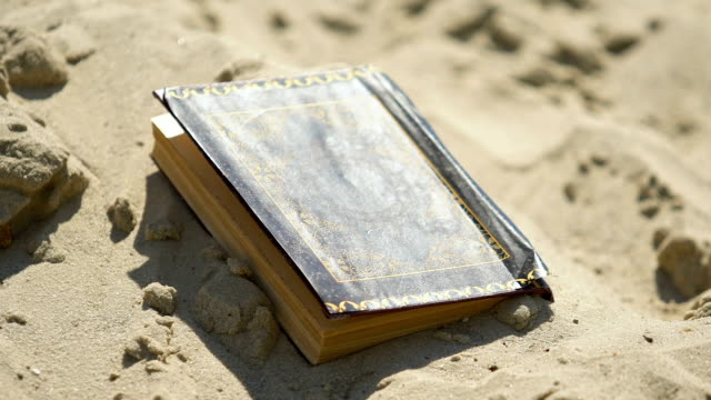 Old book Quran abandoned in sand, forgotten ancient knowledge, rejected religion