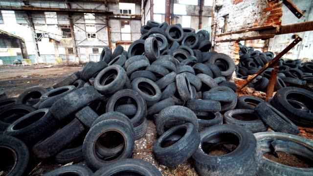 Old broken-down building inside with many tires on a large bunch. Old broken-down building inside with many tires on a large bunch. Black used rubber tires of vehicles on a desolate plant dump truck stock videos & royalty-free footage