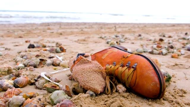 嵐の後、海のビーチで砂のラマンシェルの間で古い茶色のブーツ。 - 靴点の映像素材/bロール
