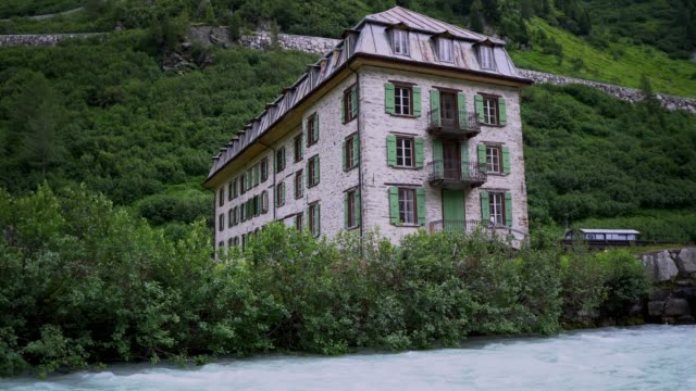 Old building near the river in Swiss Alps