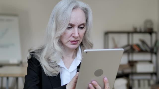 vídeos de stock e filmes b-roll de old business woman using tablet - senior business woman tablet