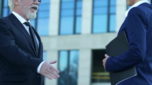 Old businessman shaking hands with sales manager, successful deal for startup