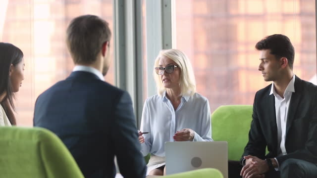 Old businesswoman talking to diverse partners at international business negotiations