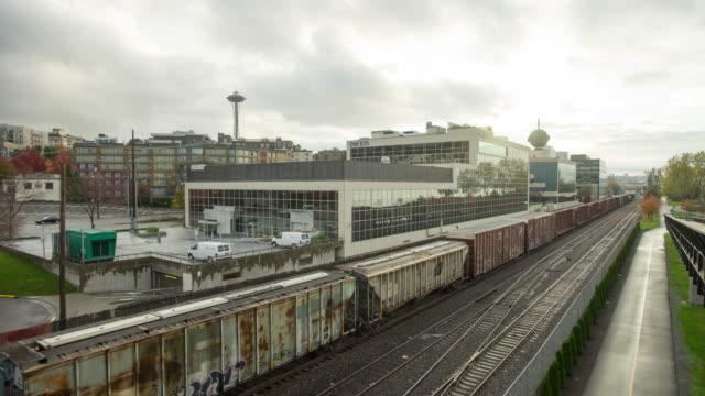 old cargo train on railways near downtown of seattle in cloudy sky. timelapse 4k