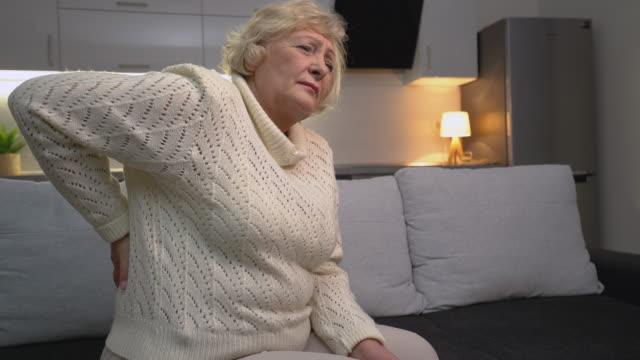 vídeos de stock, filmes e b-roll de mulher caucasiana velha que sente uma mais baixa dor traseira, inflamação dos rins, nefrologia - rim órgão interno