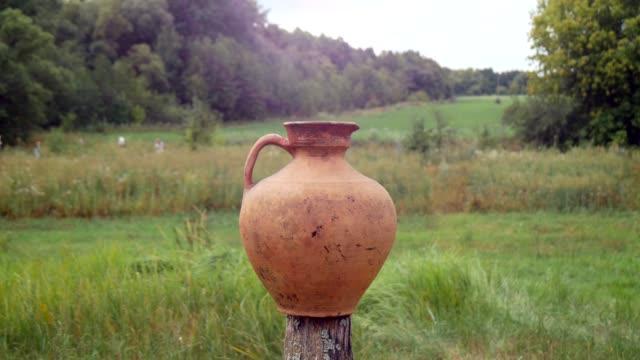 vidéos et rushes de vieille crute d'argile en céramique sur le fond de nature - picto urne