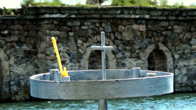 Old christian church under water with metal candlestick on the shore and cross on the rooftop video