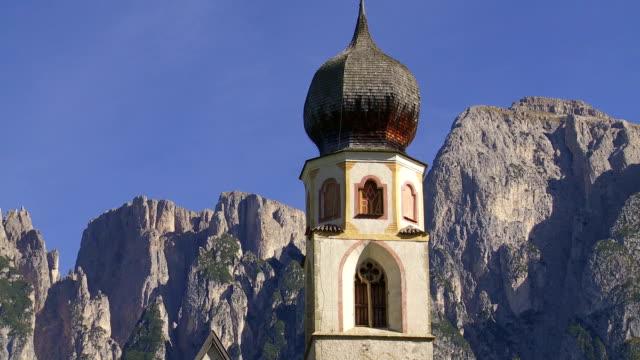 vídeos de stock, filmes e b-roll de a antiga igreja na frente das montanhas alpinas inclinação para cima - característica arquitetônica