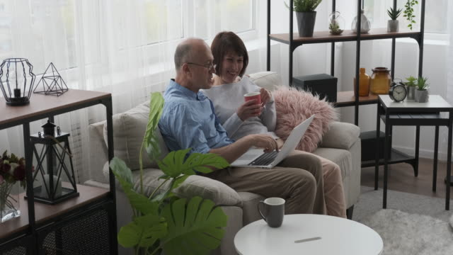Old couple using laptop and drinking coffee on sofa Happy old couple using laptop and drinking coffee on sofa at home good news stock videos & royalty-free footage