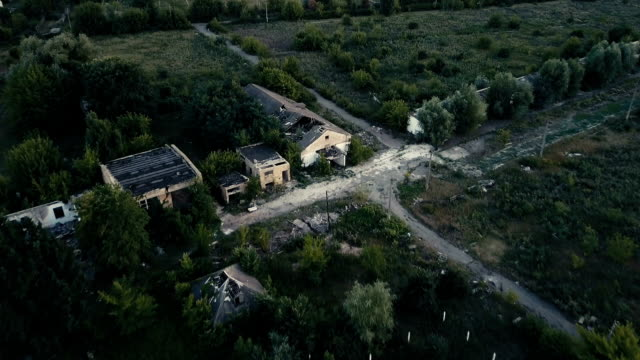 Old destroyed buildings among trees. Aerial video