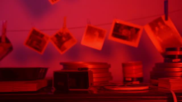 stare opracowane zdjęcia wiszące na linie w czerwonym ciemnym pokoju prywatnego laboratorium fotograficznego. czarno-białe zdjęcia drukują, ulubione hobby, odnawianie zapisów pamięci z dzieciństwa. proces tworzenia zdjęć - analogiczny filmów i materiałów b-roll