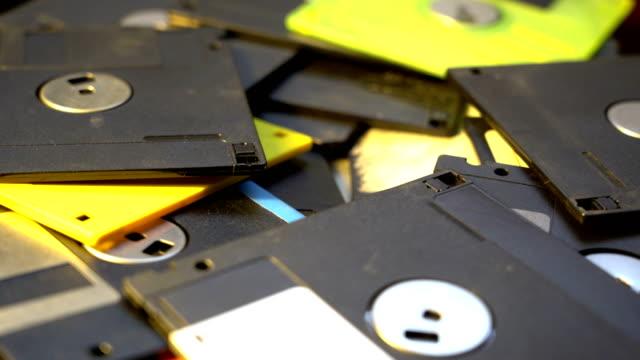 vídeos y material grabado en eventos de stock de viejos disquetes datos centro concepto fondo, pila de disquetes gira tecnología anticuada - disquete