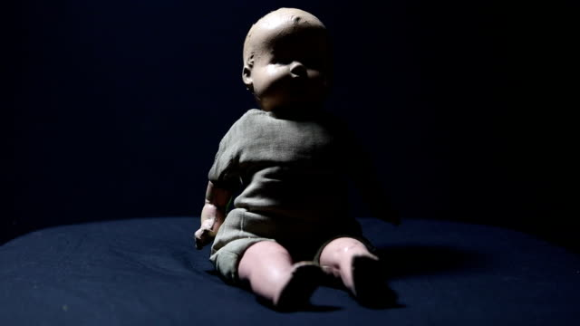 Old Doll in Creepy Lighting An creepy, cracked and dirty old antique baby doll in spooky lighting. doll stock videos & royalty-free footage