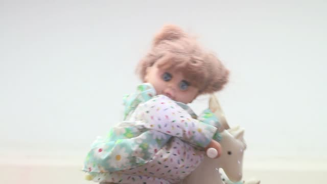 old doll on a rocking horse