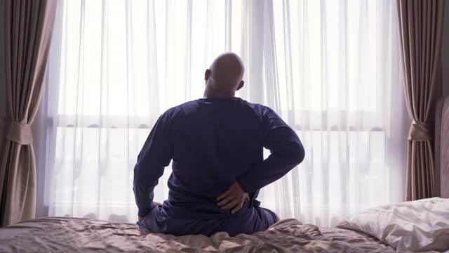 vídeos de stock, filmes e b-roll de velho idoso negro. afro-americano acordando na cama no quarto em casa no início da manhã, sofrendo de dor nas costas ou cãibra. dor nas costas. músculo machucado. síndrome do escritório. - articulação humana