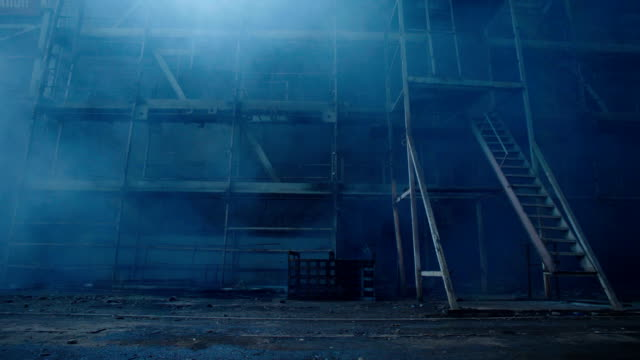 Old fabric manufactory building in the smoke. Dark Space atmosphere. Abandoned factory hall with broken glass on windows.Apocalyptic scene with destroyed warehouse. video