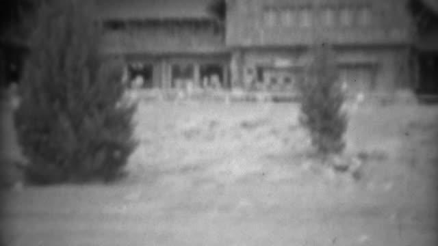 1937: Old Faithful geyser sign hotel lodge tourist crowd waiting watching.