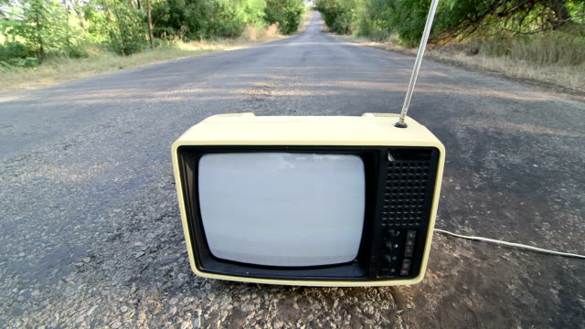 Old fashioned Tv with flickering screen on empty countryside road video