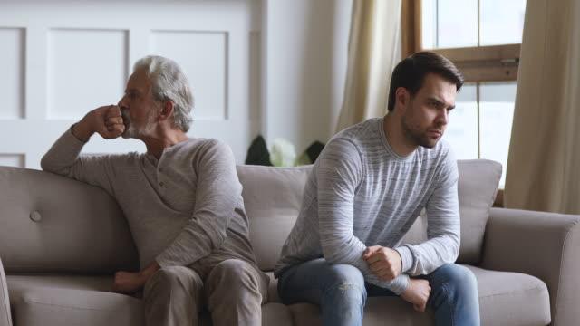 stockvideo's en b-roll-footage met oude vader en volwassen zoon draaien terug negeren elkaar - conflict