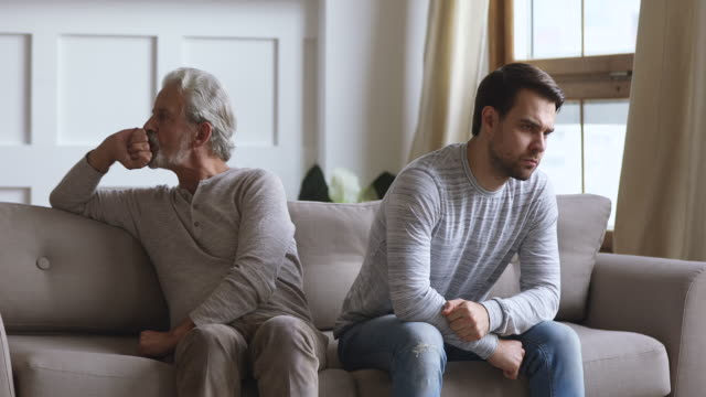 old father and adult son turn back ignore each other - walczyć filmów i materiałów b-roll
