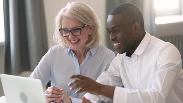 alte managerin lehrt junge afrikanische praktikantin erklären computerarbeit - employee stock-videos und b-roll-filmmaterial