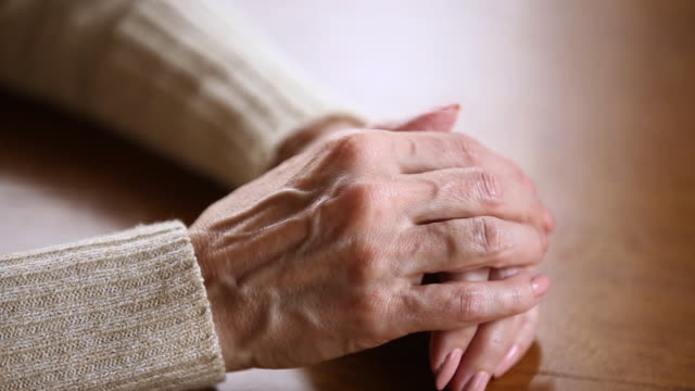 Old female wrinkled hands folded on table close up view