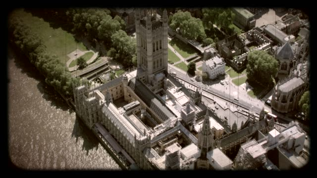 Old Film Aerial View of the Houses of Parliament, London, UK. 4K An old film aerial view of the Houses of Parliament in Westminster, London, UK. Filmed from a helicopter in full 4K in lovely sunshine. vintage architecture stock videos & royalty-free footage
