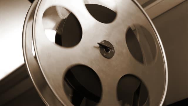 vecchio proiettore cinematografico in riproduzione in un cinema. primo-up di una bobina con un film. - cilindro video stock e b–roll
