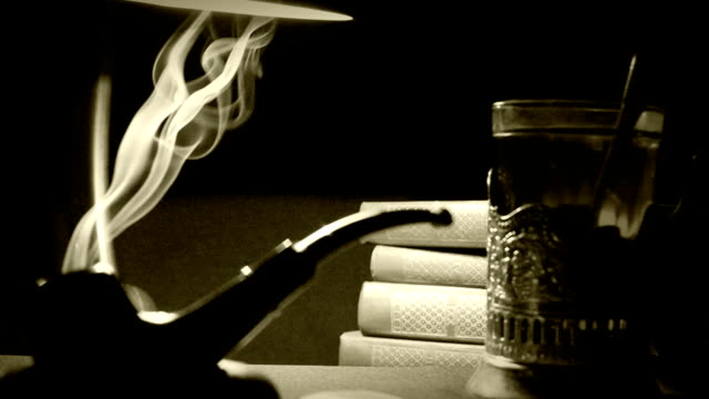 Old film styled footage of the table in a study: smoking pipe, books and tea in a glassholder video