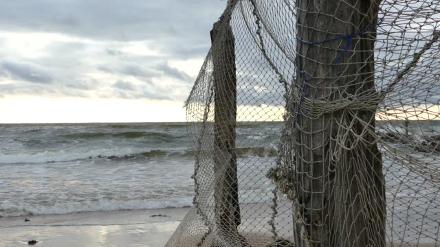 Old Fishing Net Hanging on Seaside Old Fishing Net Hanging on weathered wooden pole on Seaside. Handheld camera baltic countries stock videos & royalty-free footage