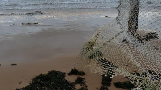 vídeos de stock, filmes e b-roll de rede de pesca velha que pendura no beira-mar - países bálticos