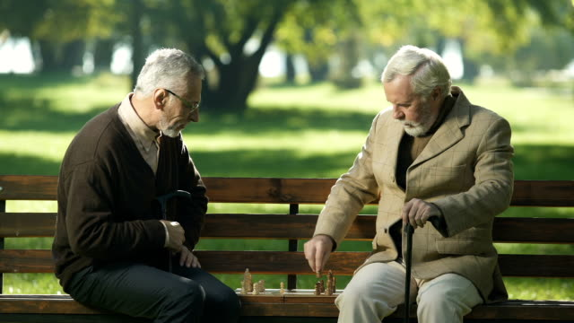 vídeos de stock e filmes b-roll de old friends sitting on bench in park and playing chess, happy leisure time - xadrez