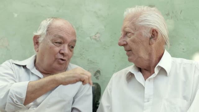 vídeos de stock, filmes e b-roll de velhos amigos, dois homens idosos conversando feliz no parque - sul europeu